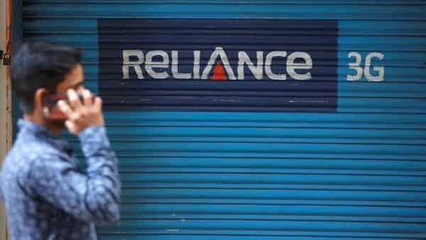 A man speaks on his mobile phone as he walks past a closed shop painted with an advertisement of Reliance Communications.  (Reuters)