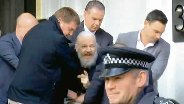 A handcuffed Julian Assange being dragged out of the Ecuadorian embassy. Photo: Reuters