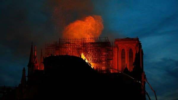 Firefighters use hoses as Notre Dame cathedral burns in Paris, France, on Monday. (Francois Mori/AFP)