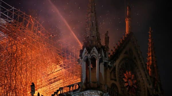Sparks fill the air as Paris Fire brigade members spray water to extinguish flames as the Notre Dame Cathedral burns in Paris, France, on Monday. (Philippe Wojazer/Reuters)