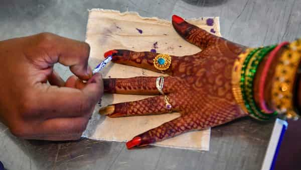 An election official applies the indelible ink on the finger of a bride at a polling station, during the 2nd phase of Lok Sabha elections in Bengaluru, yesterday (PTI)