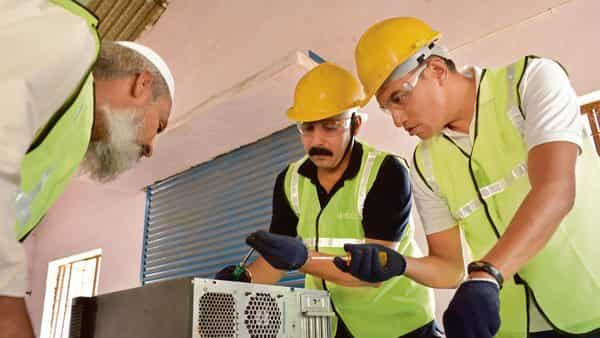 Binbag employees examine e-waste at the startup's recycling factory in Hindupur, Andhra Pradesh