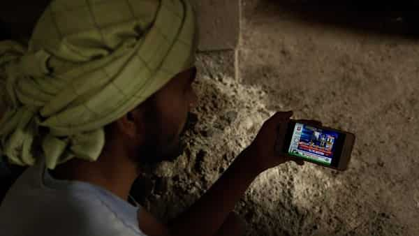 An Indian laborer at a building construction site watches election trends on a mobile phone