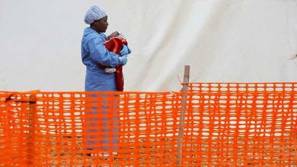 Rachel Kahindo, Ebola survivor working as a caregiver to babies who are confirmed Ebola cases, holds an infant outside the red zone at the Ebola treatment centre in Butembo, Democratic Republic of Congo (Photo: Reuters)