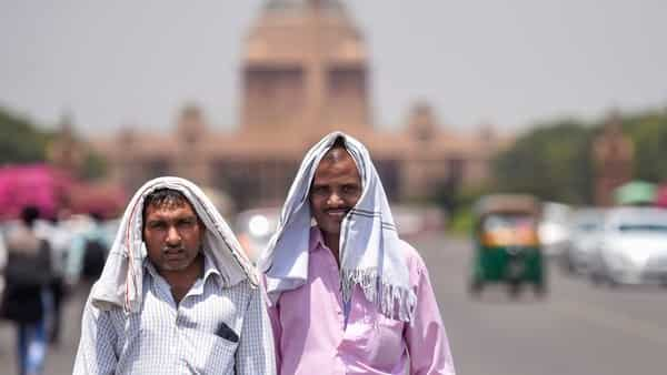 Pedestrians cover their heads to shield from the scorching sun, on a hot summer day, in New Delhi.  (PTI )