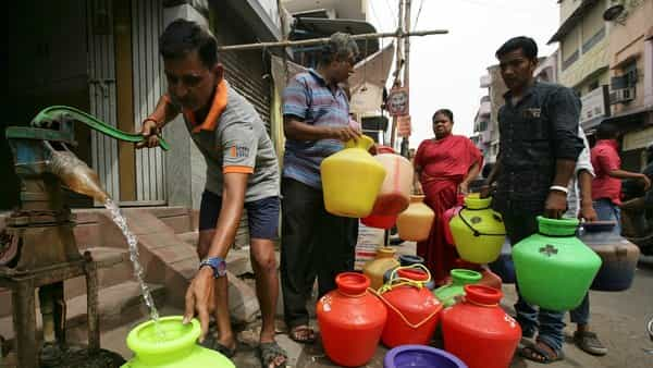 A man uses a hand-pump to fill up a container with drinking water as others wait in a queue on a street in Chennai.  (Reuters )