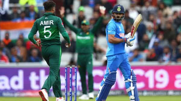 India's captain Virat Kohli, right, leaves the pitch after he is caught by Pakistan's captain Sarfaraz Ahmed, center, off the bowling of Pakistan's Mohammad Amir, left, during the Cricket World Cup match between India and Pakistan at Old Trafford in Manchester, England, on 16 June, 2019. (Photo: AP)
