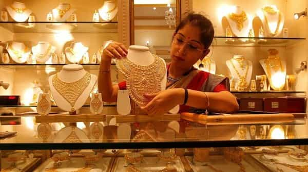 A saleswoman displays a gold necklace inside a jewellery showroom.  (Reuters )
