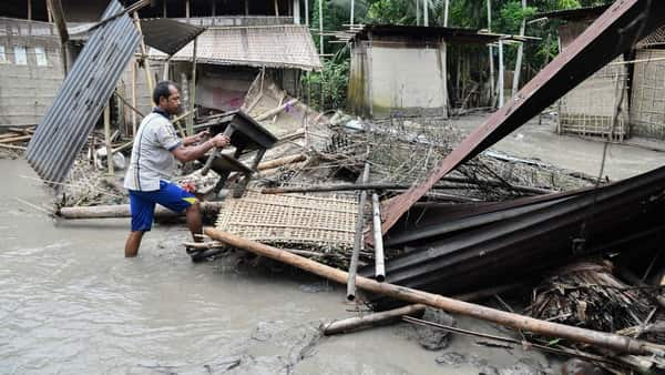 A woman searches her belongings near the debris of her house following floodwaters in Kasuarbori village, in Assam on Saturday (AFP)
