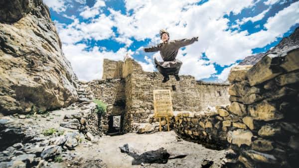 A young boy jumps outside the community-run museum in Henasku. (Priyanka Parashar/Mint)