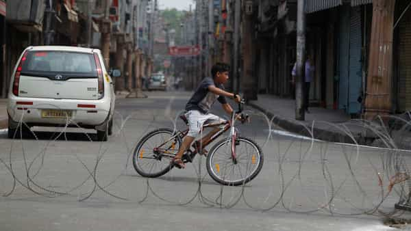 A boy rides a bicycle past a barbed wire erected as part of security restrictions in Jammu on Tuesday (AP)