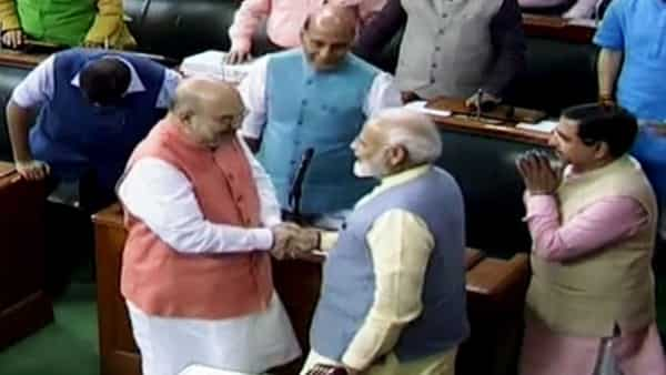 Prime Minister Narendra Modi greets Union Home Minister Amit Shah after the Jammu and Kashmir Reorganisation Bill and Resolution to revoke Article 370 was passed by Lok Sabha,  (ANI)