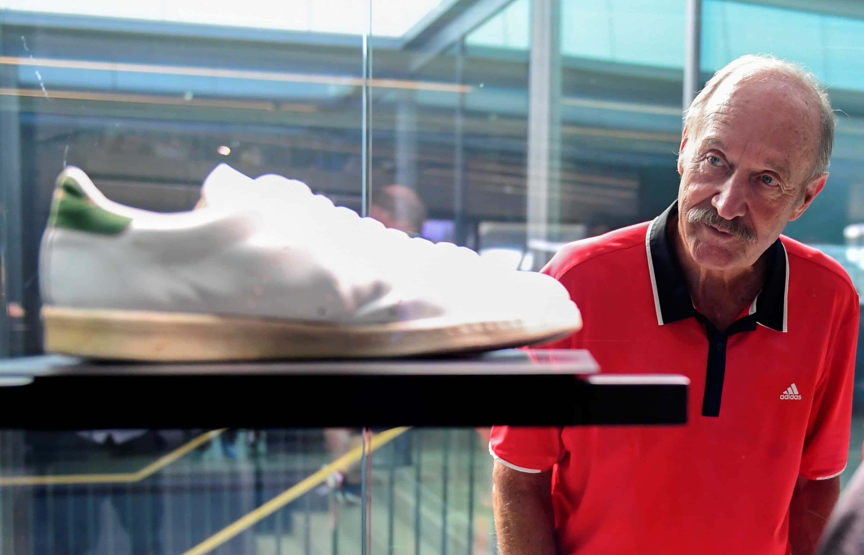 Former tennis player Stan Smith looks at his shoe as he attends the celebrations for German sports apparel maker Adidas' 70th anniversary at the company's history exhibition in Herzogenaurach, Germany. (Reuters)