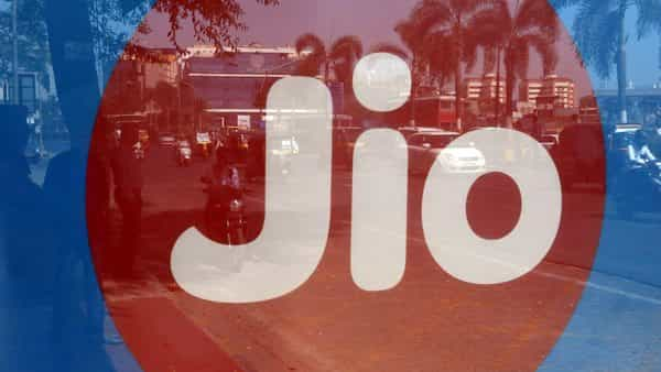 Commuters' reflections are seen on an advertisement for Reliance Industries' Jio telecoms business at a bus stop in Mumbai.  (Reuters)