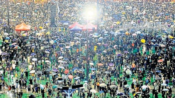 Hong Kong protesters defy heavy rains, throng streets