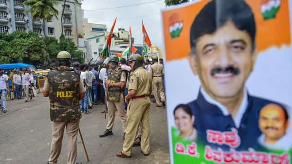 Police personnel stand guard as Congress party members raise slogans against the central government for the arrest of Congress leader D.K. Shivakumar by ED officials, in Bengaluru, Wednesday (Photo: PTI) (PTI)