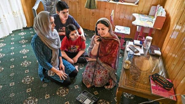 A Kashmiri family in Srinagar talks to relatives on a landline phone on 17 August.