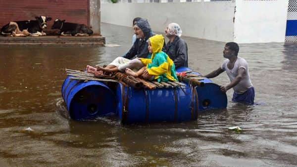 People sit on a makeshift boat to cross the flood-affected area of Sakha Maidan following heavy monsoon rainfall, in Patna (Photo: PTI)