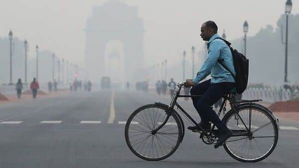 A man rides a cycle past the India Gate on a smoggy morning in New Delhi. (Photo: Reuters)