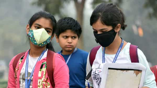 Children cover their face with a mask to protect from air pollution in New Delhi. (ANI )