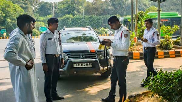 Traffic policemen impose penalty on a traffic offender for riding a vehicle with a number plate ending with an even digit during the Odd-Even scheme, in New Delhi, on Tuesday. (PTI)