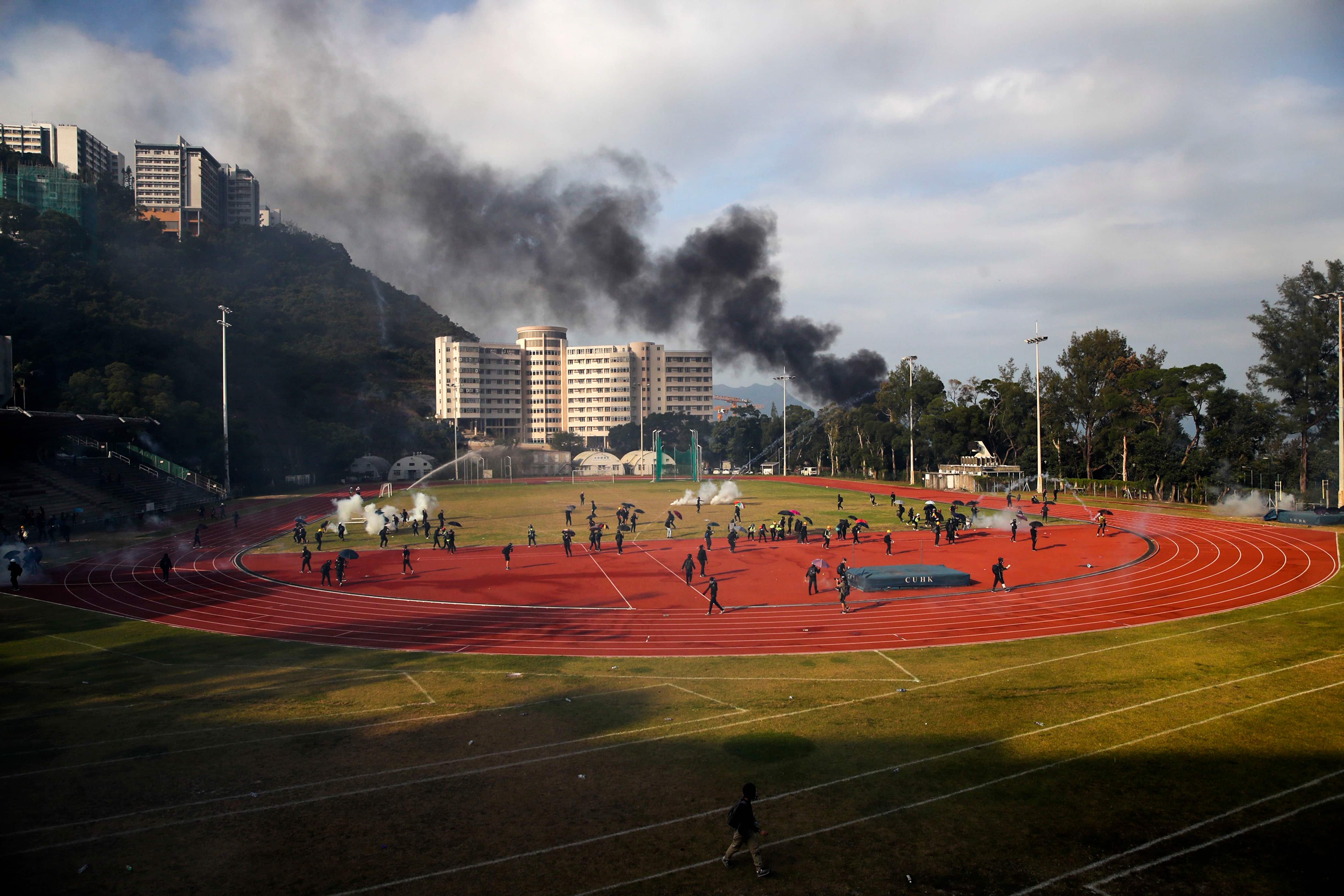 Students try to clear the tear gas canisters on a field during a face-off with police at Chinese University in Hong Kong (Photo: AP)