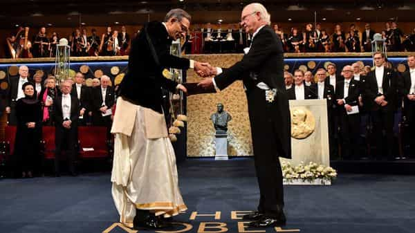 American economist Abhijit Banerjee shakes hands with Sweden's King Carl Gustaf as he receives the Sveriges Riksbank Prize in Economic Sciences in Memory of Alfred Nobel during the Nobel Prize award ceremony at the Stockholm Concert Hall in Stockholm, Sweden