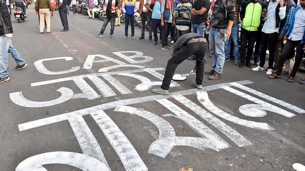 An activist writes on a street during a protest against Citizenship Amendment Act 2019, in Guwahati (Photo: ANI)