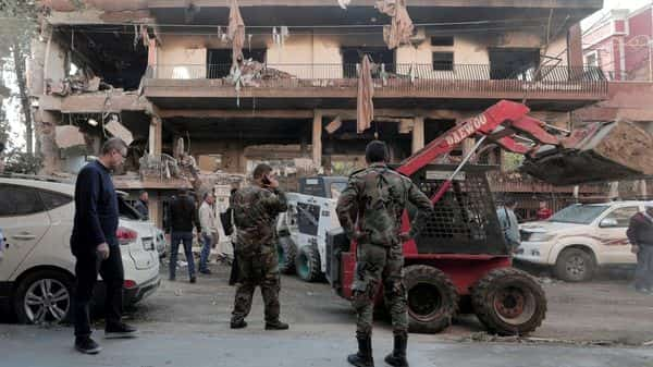 Syrian soldiers stand near a damaged building in Mezzah, Damascus (Photo: Reuters)