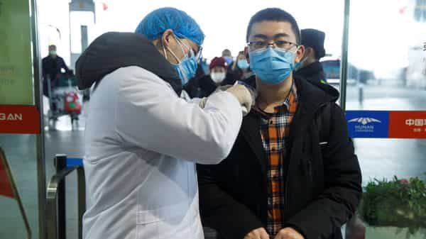 A medical official takes the body temperature of a man at the departure hall of the airport in Changsha, Hunan Province.  (Reuters)