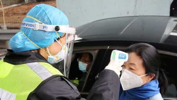 FILE PHOTO: A security officer in a protective mask checks the temperature of a passenger  (REUTERS)