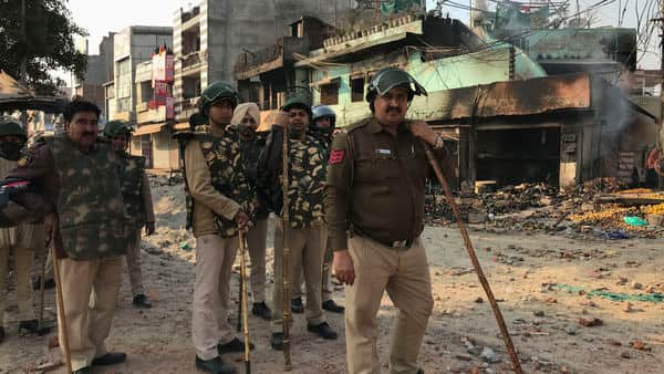 Indian policemen guard an area vandalized following violence between two groups in New Delhi. (Photo: AP)