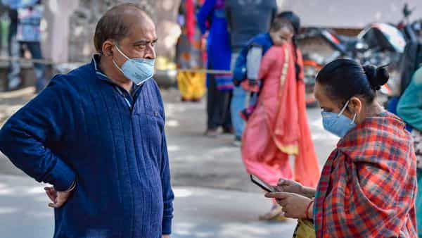 People wearing protective masks in the wake of novel coronavirus or COVID-19 outbreak, stand outside RML Hospital in New Delhi on Tuesday. (PTI)