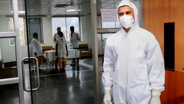 A medical official wears a protective suit and a mask to mitigate the spread of coronavirus inside a ward, specialised to receive virus-infected patients, at LNJP Hospital in New Delhi (PTI)