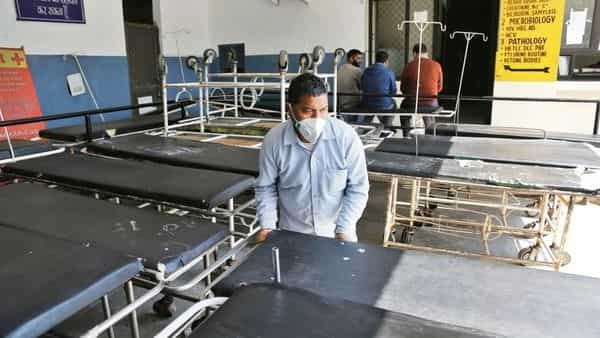 A hospital staff arranges trolleys at the Government Medical College in Jammu on Sunday (Photo: AP)