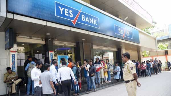 Account holders stand in a queue to withdraw money from Yes Bank, in Surat.