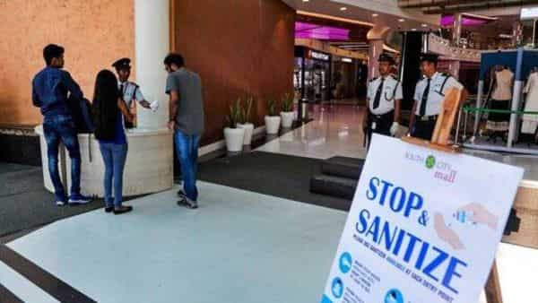 Security guards checks bags and offers hand sanitizer to the visitors beside a poster as a precautionary measure against Covid-19 in an almost empty shopping mall in Kolkata on Sunday (Photo: AP)