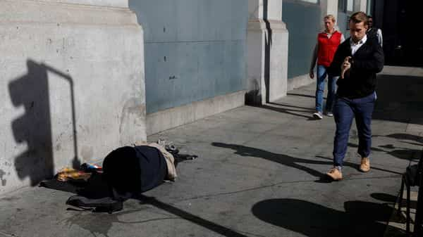 People walk by a homeless person laying on the sidewalk in San Francisco (Photo: Reuters)