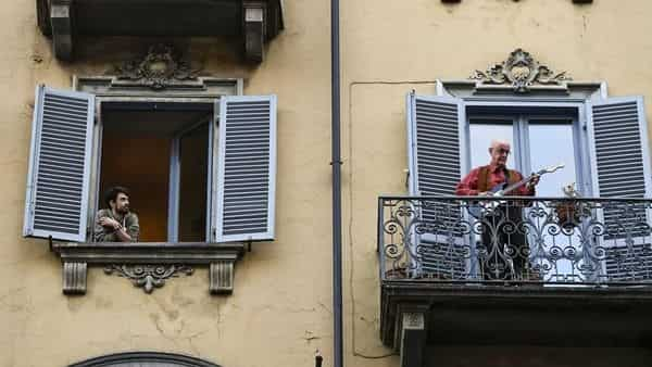 A man playing his guitar from the balcony of his home as neighbours look on.
