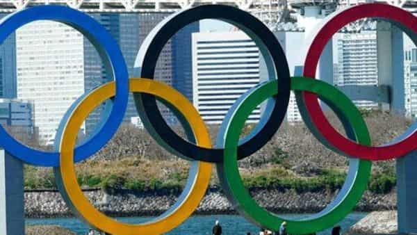 Workers stand at the bottom of the Olympic rings at Tokyo's Odaiba district. The Tokyo Olympics are probably going to happen, but almost surely in 2021 rather than in four months as planned.  (AP)