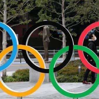 A man wearing protective face mask, following the outbreak of the coronavirus, is seen through The Olympic rings in front of the Japan Olympics Museum in Tokyo, Japan, (REUTERS)
