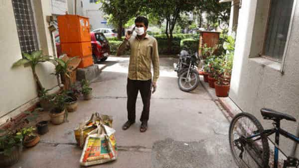 A grocery shop employee, wearing face mask as a precaution against coronavirus, calls a customer living on the second floor to come down to receive their delivery in New Delhi (Photo: AP)