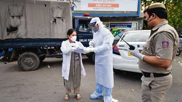 Medics, in protective suits, interact as police cordon off an area in Nizamuddin after some people showed coronavirus symptoms, in New Delhi on Monday. (Photo: PTI)