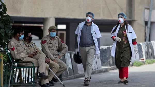 Policemen guard as Indian doctors wearing masks walk inside Government Medical College hospital in Jammu (AP)