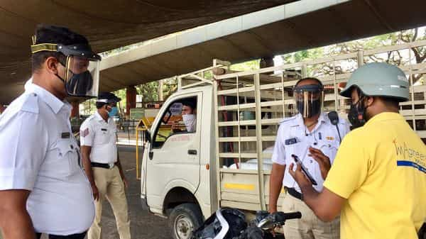 Traffic police wears visors on the face mask while checking vehicles during the nationwide lockdown amid coronavirus pandemic, in Bengaluru. (ANI)