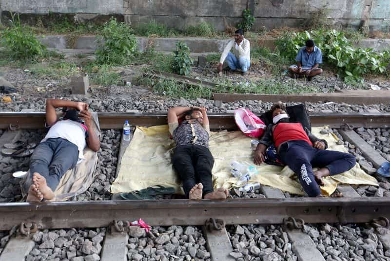 FILE PHOTO: Migrant workers rest on a railway track during a 21-day nationwide lockdown to slow the spreading of coronavirus disease (COVID-19) in in Mumbai.