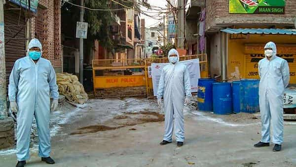 Police personnel wearing protective suits stand guard at a Covid-19 containment zone in South Delhi (Photo: PTI)