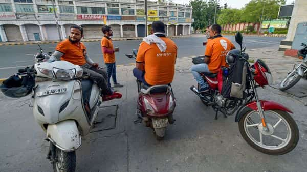 New Delhi: Deliverymen of food aggregator Swiggy wait along a roadside during the nationwide lockdown in wake of the coronavirus pandemic, in New Delhi, Monday, April 13, 2020. (PTI)