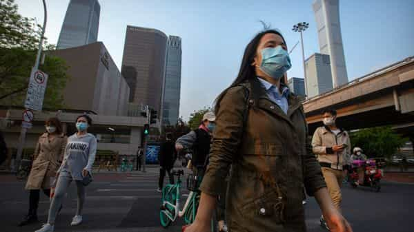 People wearing face masks to protect themselves against the spread of the new coronavirus cross an intersection in the central business district in Beijing (Photo: AP)