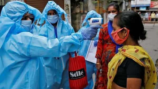 A health worker wearing protective gear uses an infrared thermometer to check the temperature of a woman in a residential area in Kolkata (Reuters)